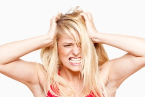 angry, frustrated girl with hands in her hair screaming - isolated on white